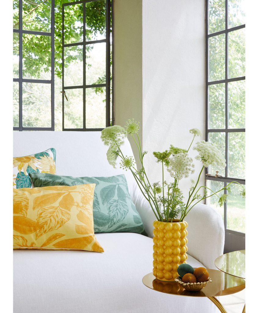 biela sedačka s farebnými vankúšmi a žltou vázou na zlatom okrúhlom stolíku