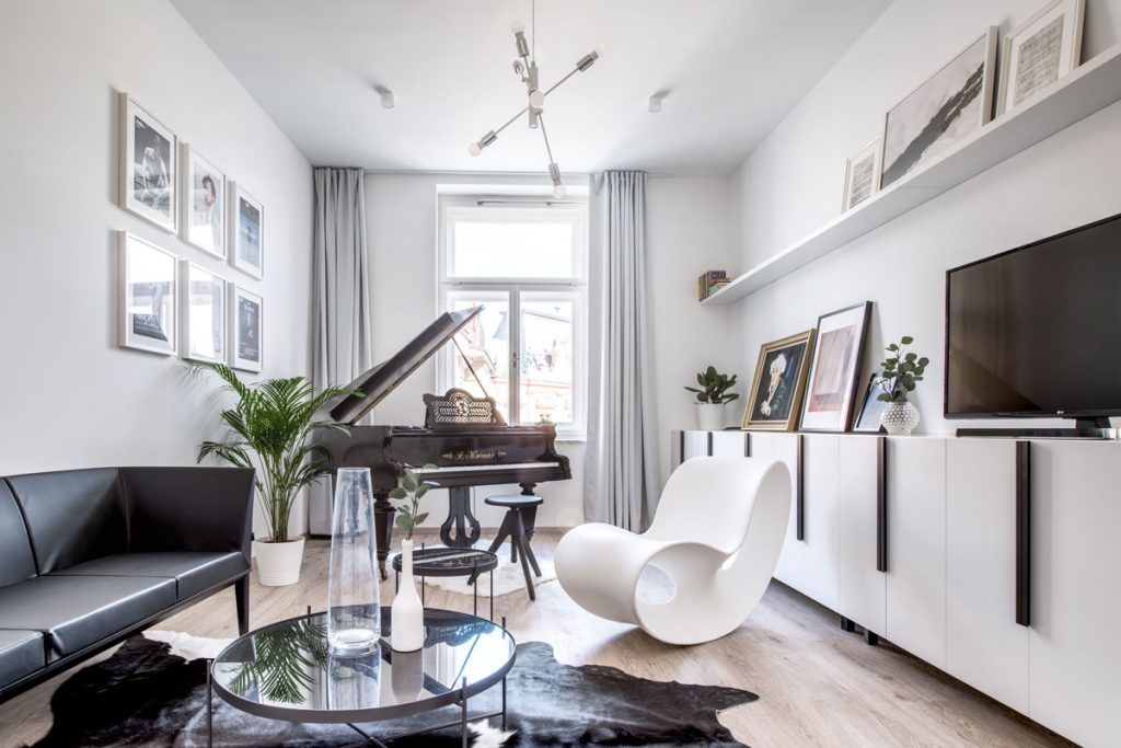 Bielo-čierno-hnedá kombinácia farieb v apartmáne v bohémskom štýle. Zariadený s klavírom, bielym hojdacím dizajnovým kreslom, koženou sedačkou a kravskou kožou.