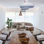 retro obývačka prepojená s jedálňou v zemitých farbách, s drevom, zeleňou a radom svietidiel