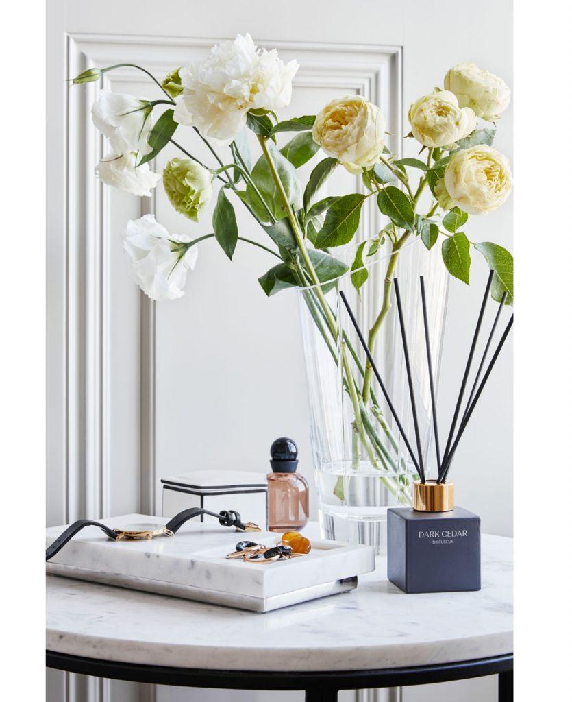 sklenená víáza s kvetmi na mramorovom stolíku