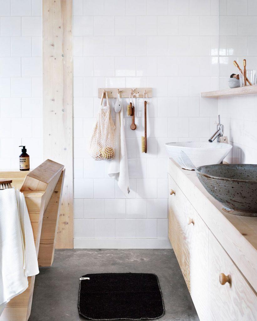 kúpeľňa s bielym obkladom, drevenými skrinkami, umývadlom určeným na dosku a pomôckami zavesenými na stene
