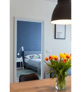 Spálňa v severskom štýle situovaná oproti jedálenskému stolu. Tlmené farby oživuje zelený koberec a vankúš.