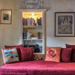 červené posedenie so zabudovanou knižnicou v stene s ozdobnou štukou