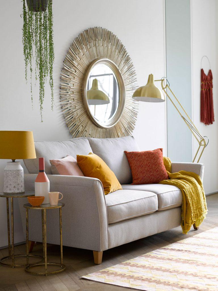 interiér v boho štýle zariadený v bielych tónoch s farebnými doplnkami, na stene s veľkým kruhovým zrkadlom