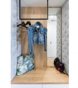 komora s posuvnými dverami a čalúnenými panelmi na bočných stenách a s kovovou tyčou umiestnenou zo stropu, ktorá slúži na vešanie oblečenia