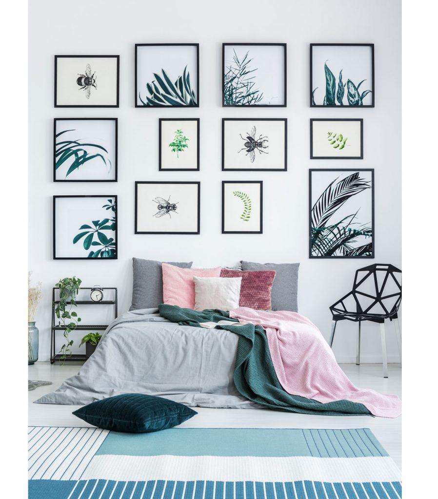 viacero obrazov rozvešaných na stene v spálni