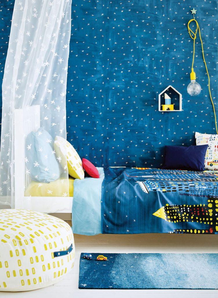 detská posteľ s modrými obliečkami a hviezdnou oblohou na bočnej stene