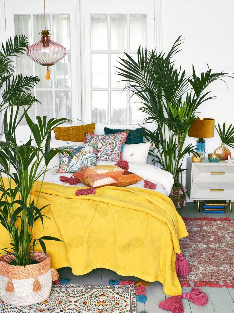 spálňa v boho štýle s textíliami živých farieb ako výrazná žltá, oranžová, kráľovská modrá
