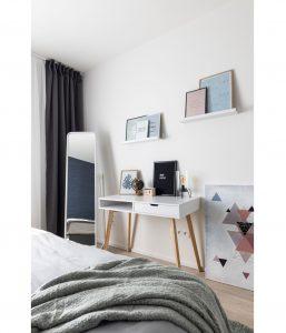 Spálňa v škandinávskom štýle, s jednoduchým dreveným stolíkom a zrkadlom v životnej veľkosti. Na poličkách sú položené obrazy.