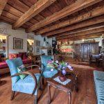 historizujúci interiér s drevenou podlahou a stropnými trámami, zariadený masívnym historickým nábytkom
