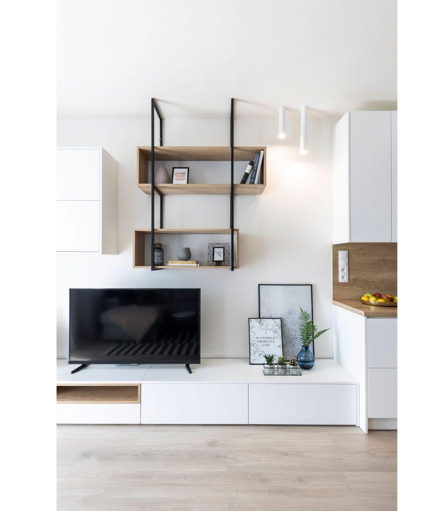 biela kuchynská linka prechádza plynule do televíznej skrinky, nad skrinkou sú jednoduché drevené police zasadené do kovovej konštrukcie