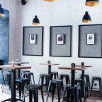 industriálny interiér s kovovými prvkami na nábytku a dekoráciách, s využitím ťahokovu na závesných fotografiách