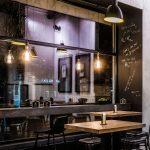 industriálna reštaurácia U Tomana s barovým pultom umiestneným pred nadrozmerným oknom