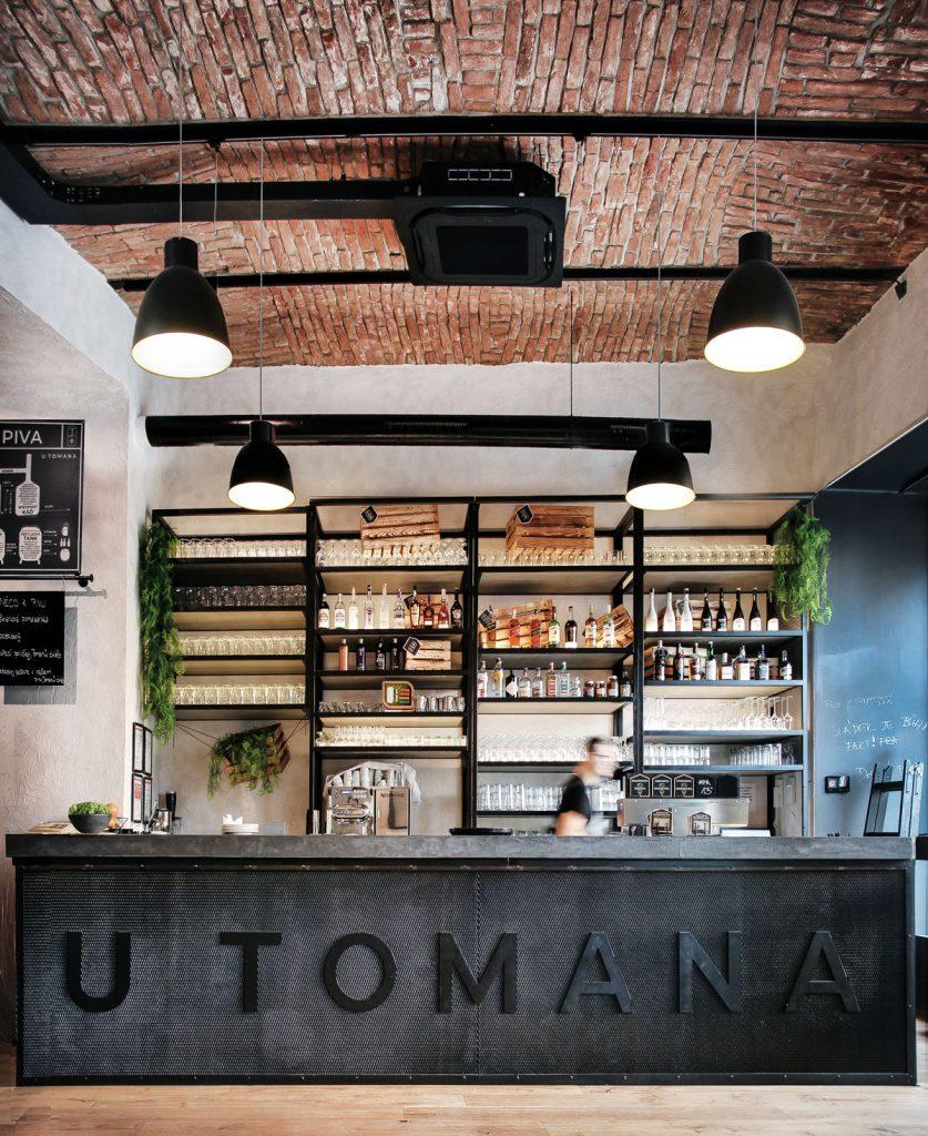 barový pult v reštaurácii U Tomana v industriálnom štýle s tehlovým stropom a veľkým kovovým regálom