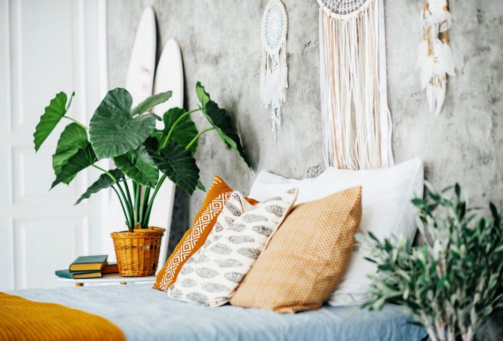 boho spálňa s kvetinami a lapačmi snov na stene