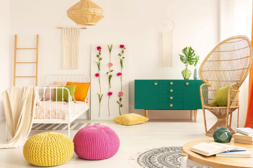 interiér s pleteným kreslom, pletenou lampou, pufmi a závesnými dekoráciami