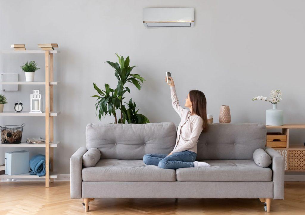 žena sediaca na gauči nastavuje klimatizáciu