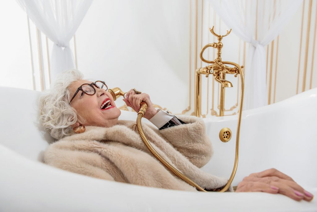 veselá dôchodkyňa vo vani telefonuje cez ručnú sprchu