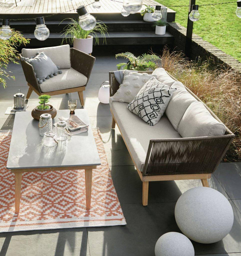 terasa s jednoduchým moderným retro nábytkom a oranžovobielym kobercom so vzorom