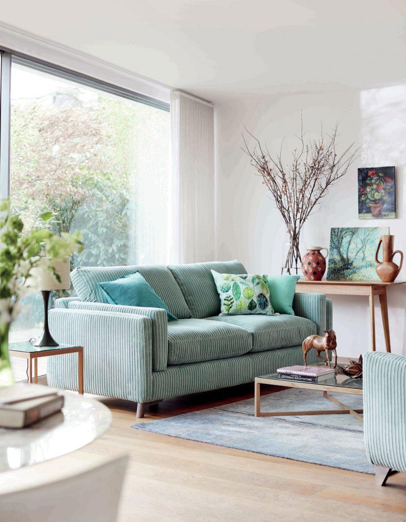 obývačka s mentolovou pohovkou, drevenými stolíkmi a prírodnými dekoráciami