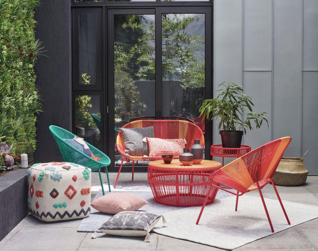 terasa s farebnými pletenými kresielkami a stolíkom v červenooranžovej a tyrkysovej farbe, s vankúšmi a taburetkou na sedenie