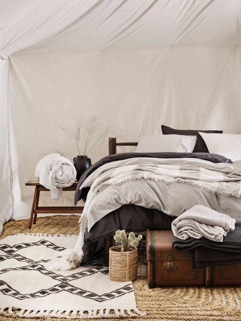 spálňa v prírodnom štýly, s bavlneným posteľným prádlom, rotangovým kvetináčom a vzorovaným vlneným kobercom