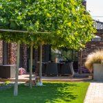 rodinný dom s tehlovým obkladom, terasou so záhradným sedením a betónovými vyvýšenými záhonmi, v ktorých je vysadená okrasná tráva