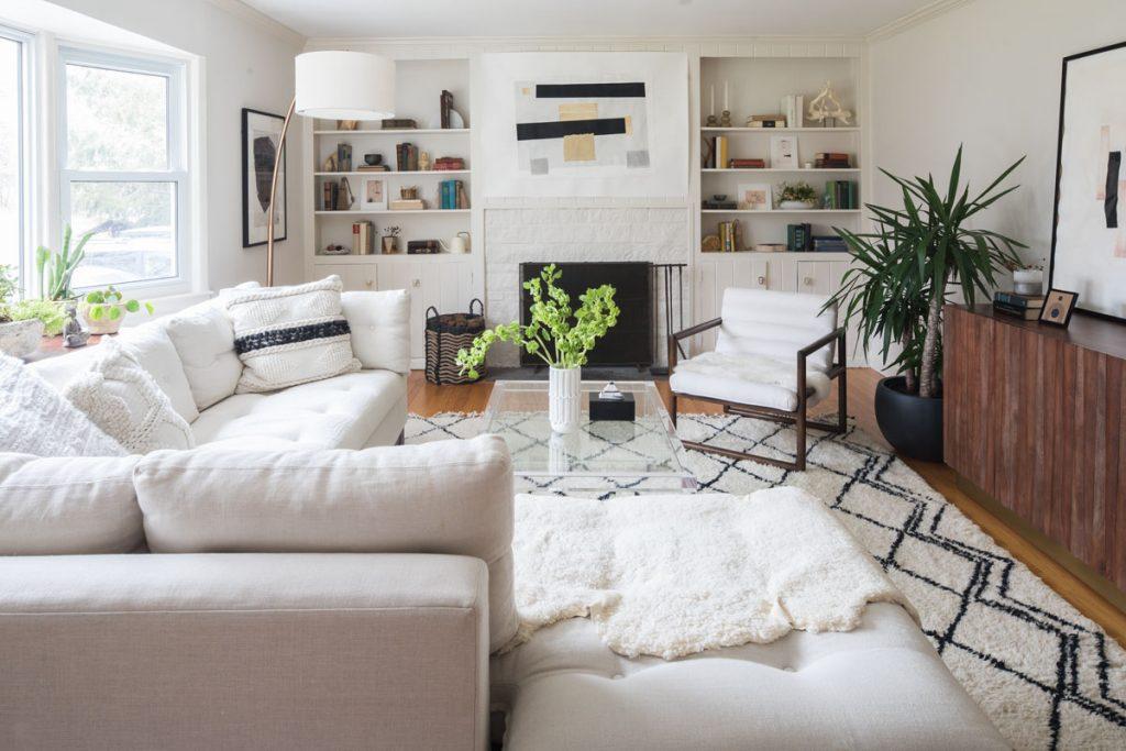 vidiecka obývačka s retro nábytkom, ladená v prírodnom štýle, biely gauč a kreslo, tmavohnedá drevená komoda, biela knižnica zabudovaná v stene, kozub a veľký vlasový koberec so vzorom
