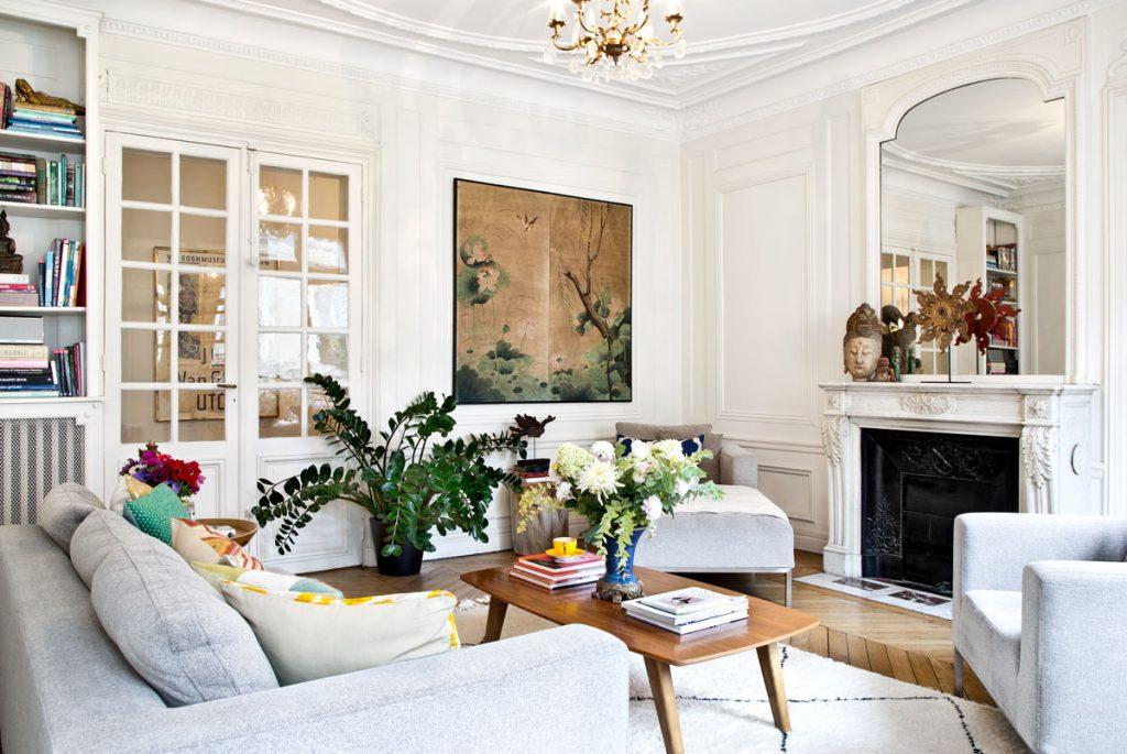Obývačka zariadená v retro modernom štýle, s drevenými parketami, kozubom so štukovanou výzdobou a veľkým zrkadlom. V interiéri sa kombinuje azijský štýl s historickým a retro štýlom.