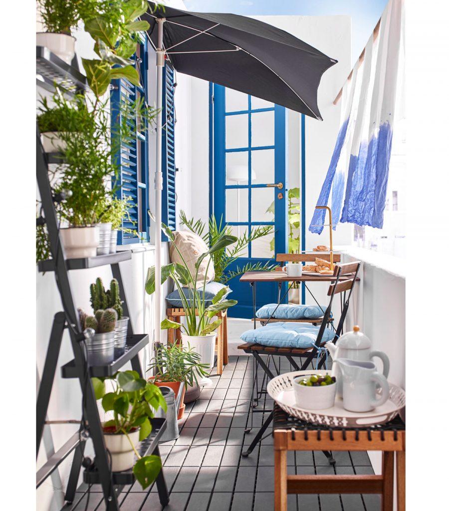 balkón so záhradným sedením, slnečníkom a rebríkom na kvetiny