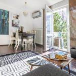 mix štýlov v obývačke: konferenčný stolík z Marakéša, rustikálna vintage komoda, retro jedálenský stôl z tmavého dreva so smotanovými drevenými stoličkami
