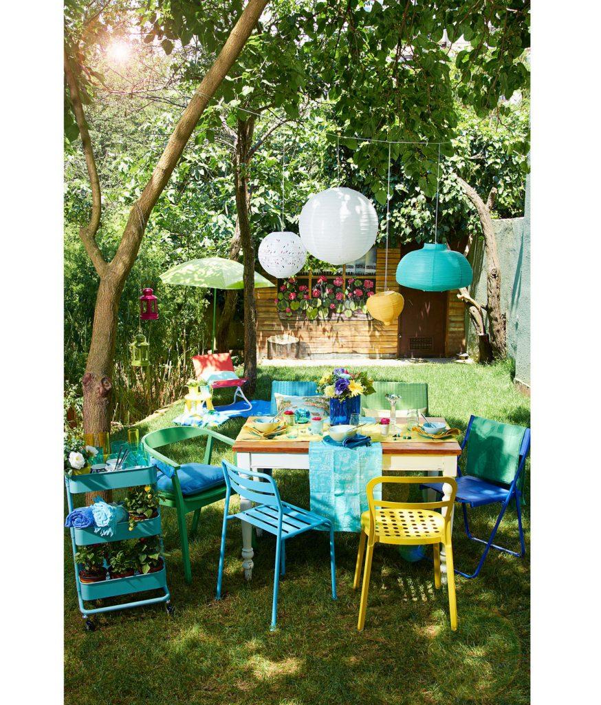 záhradné sedenie so stoličkami v žltej, modrej a zelenej farbe, s dreveným stolom, úložným regálom na kolieskach a papierovými lampiónmi zavesenými nad stolom