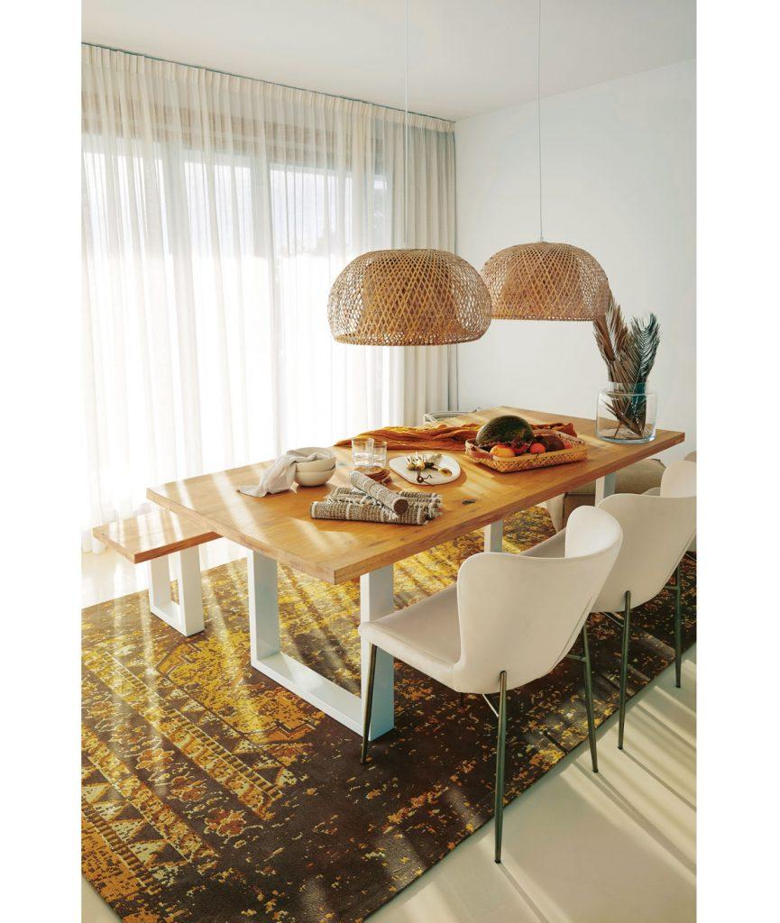 naturálna jedáleň zariadená s mohutným dreveným stolom, pletenými lustrami, bielymi stoličkami a veľkým vzorovaným kobercom v zemitých tónoch