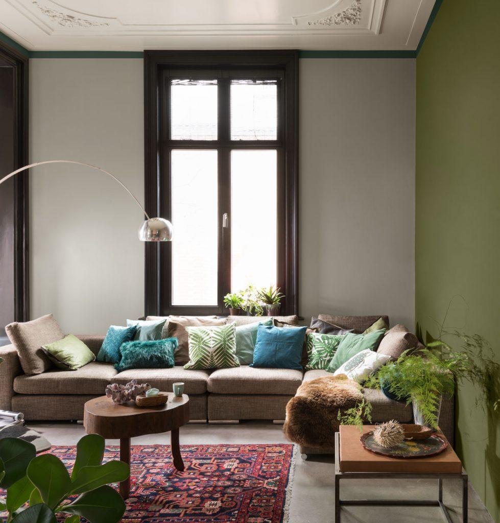 obývačka so zelenou stenou, v ktorej je vzorovaný koberec, veľký gauč s farebnými vankúšmi a dva drevené stolíky