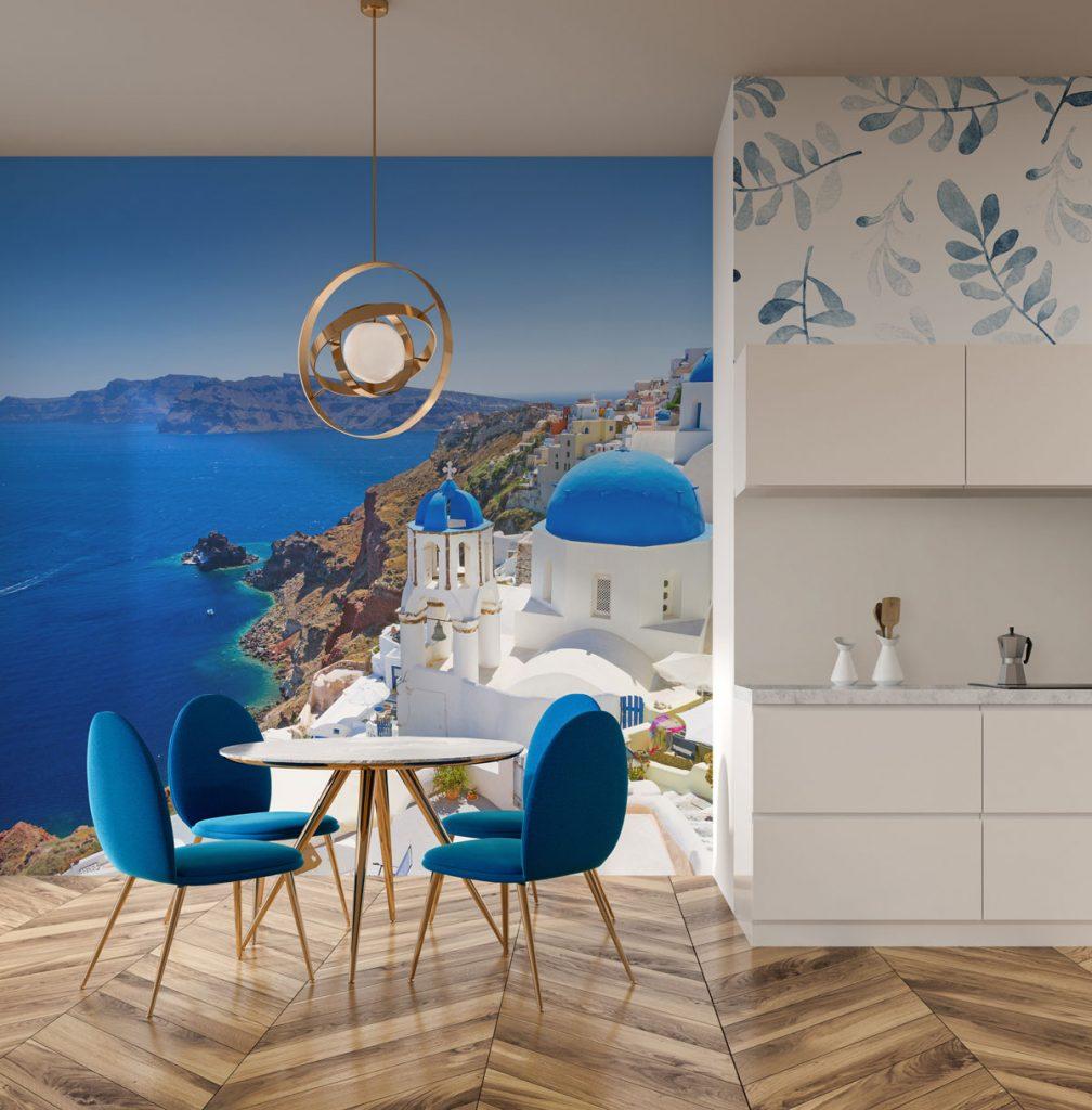 interiér v námorníckom štýle, s modrými stoličkami, okrúhlym stolom, zlatým lustrom a veľkoformátovou tapetou Santorini