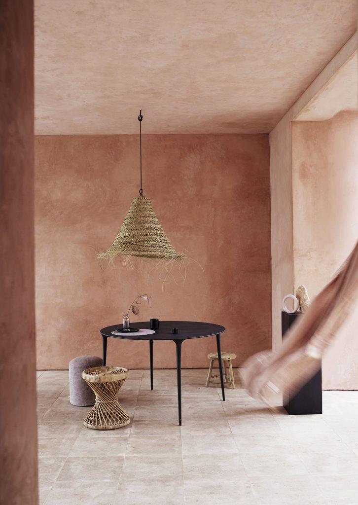 mix severského a bohémskeho štýlu v interiéri s dizajnovým čiernym stolom, pleteným prúteným lustrom a ratanovou stoličkou