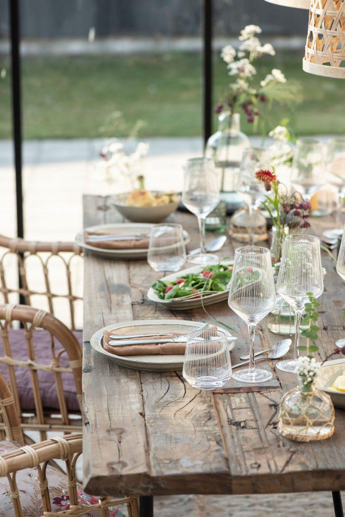 stolovanie s plytkými taniermi, so sklenenými pohármi na víno a pohármi na vodu