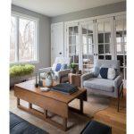 obývacia miestnosť s retro sivými kresielkami a retro skladacím masívnym stolíkom. interiér je prepojený presklenými dverami s druhou miestnosťou