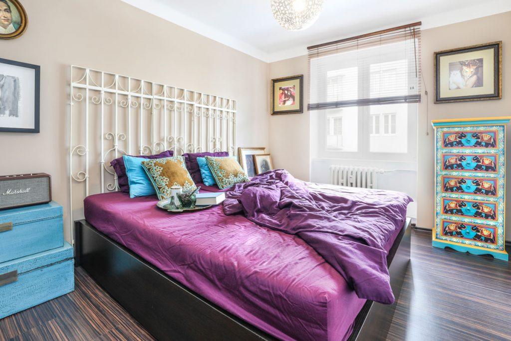 spálňa s výraznými farbami v odtieňoch fialovej, tyrkysovej, či žltej, s posteľou s kovovým čelom a s komodou s motívmi slonov