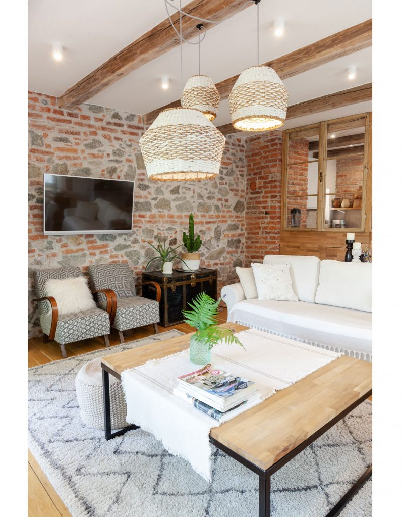 obývačka s tehlovou stenou, priznanými trámami, so zariadením v prírodných materiáloch