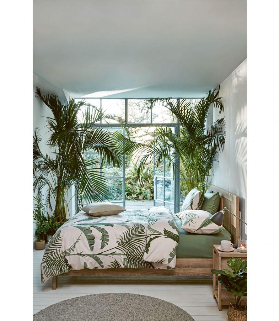 Spálňa s presklenými dvojkrídlovými dverami ladená do zelenej s motívmi listov na posteľnom prádle. Súčasťou interiéru sú aj veľké palmy.