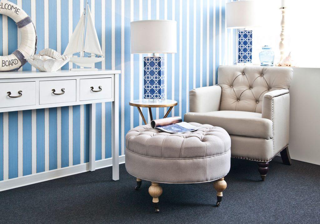 kútik na oddych so sedačkou a taburetkou, s pruhovanou modrobielou tapetou a námorníckymi dekoráciami