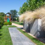 záhrada s detským ihriskom, vyvýšenými betónovými záhonmi s posadenou okrasnou trávou a s chodníkom z veľkoformátovej dlažby
