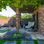 rodinný dom s terasou, na ktorej je umiestnené hojdacie kreslo, záhradné sedenie, solárna sprcha a lehátka