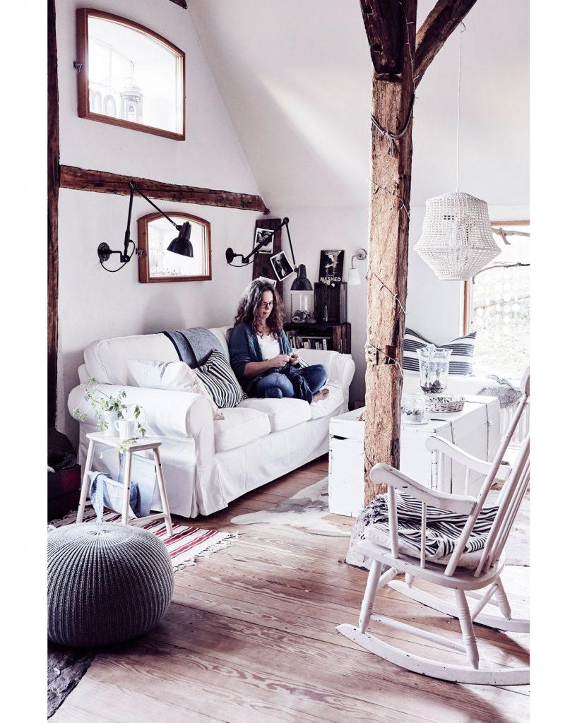 vidiecka obývačka v severskom štýle, v bielej farbe, hojdacím kreslom a priznanými trámami