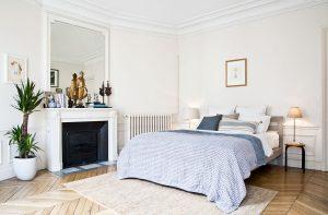 Jednoducho a účelne zariadená spálňa s kozubom, posteľou a nočným stolíkom. Na rímse kozubu je zátišie z kníh, váz a sošiek a veľké zrkadlo.