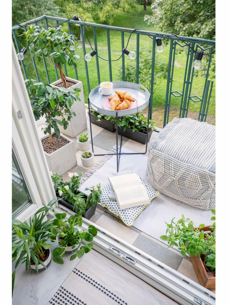 balkón s vankúšovým sedením, okrúhlym stolíkom a hranatými kvetináčmi
