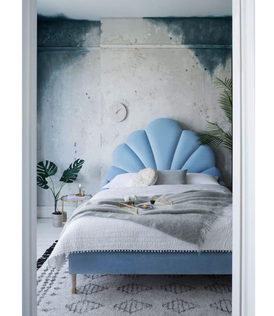 námornícka glamour spálňa s čelom postele v tvare mušle a s textíliami v modrých a sivých odtieňoch
