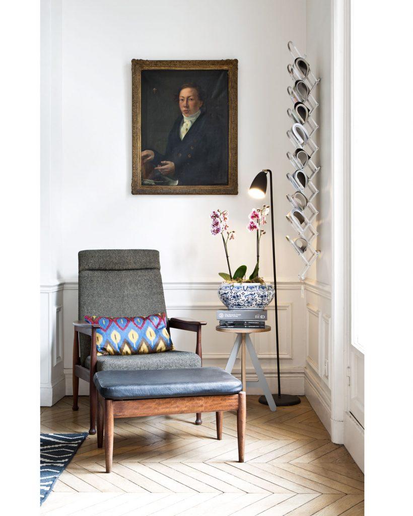 miestnosť s kazetovým obložením zariadená s obrazom s tradičným portrétom a retro kreslom spríručným stolíkom, moderným stojanom na časopisy aminimalistickou lampou