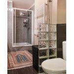 wc predelené od sprchového kútu sklobetónovými tvárnicami, pred sprchovacím kútom je orientálny koberec
